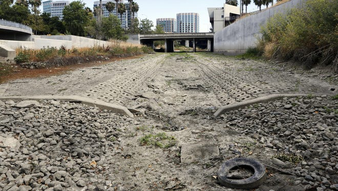The dried-up bed of the Guadalupe River in San Jose, Calif. A new study says dying wildlife, bigger wildfires and drying-up farm towns will be the biggest crises if California's drought continues.