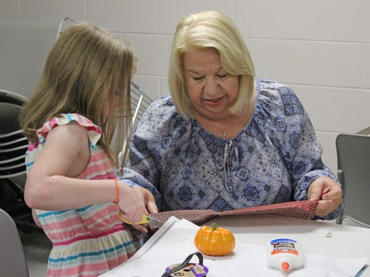 Joyce Burns and her granddaughter, Stella Weil, 7, set to work making the skirt for Stella's pumpkin witch.
