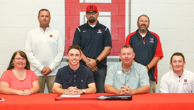 Heritage senior Cody Baker poses with school officials and family members during his recent signing.