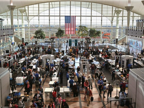 Passengers move through a main security checkpoint at the Denver International Airport. The airport is banning marijuana possession even though it is now legal in Colorado.