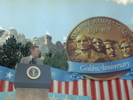 A giant replica of a coin commemorating the 50th anniversary of Mount Rushmore graces the stage near U.S. President George H. Bush who spoke at the formal dedication ceremonies of the famous monument, Wednesday afternoon, July 3, 1991 in Mount Rushmore.