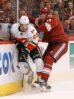 Calgary Flames' Sean Monahan (23) plays the puck off the boards as he is hit by Arizona Coyotes' Martin Hanzal, of the Czech Republic, during the second period of an NHL game Saturday, Nov. 29, 2014 in Glendale, Ariz.