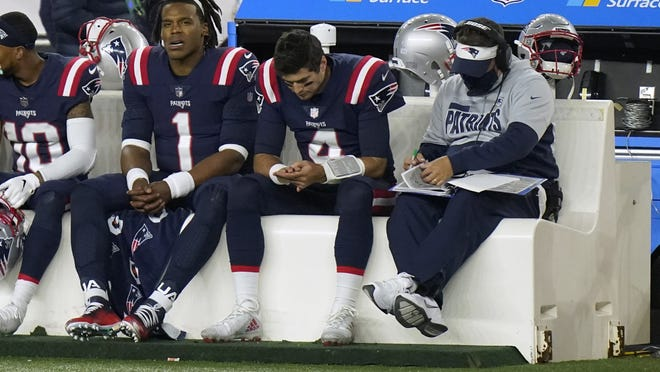 New England Patriots quarterbacks Cam Newton (left) and Jarrett Stidham sit on the bench with offensive coordinator Josh McDaniels (right) in the second half of the Patriots' loss to the San Francisco 49ers on Sunday in Foxborough.