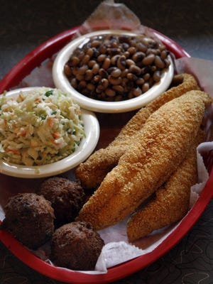 The small Catfish Basket at Soul Fish Cafe includes catfish dusted with cornmeal and fried to golden brown, served with french fries, hushpuppies, and coleslaw.