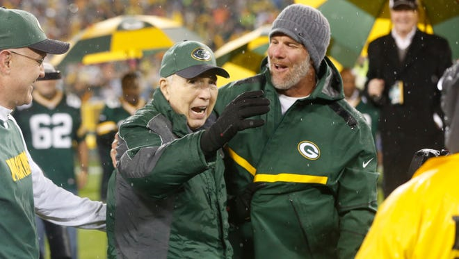 Brett Favre smiles with Bart Starr during a ceremony at halftime of an NFL football game between the Green Bay Packers and Chicago Bears Thursday, Nov. 26, 2015, in Green Bay, Wis.