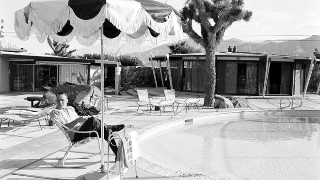 "Frank Sinatra (1915-1998) sits in a deck chair beside the pool at his Palm Springs home and reads a script or his film ""Marriage on the Rocks"" in 1965."