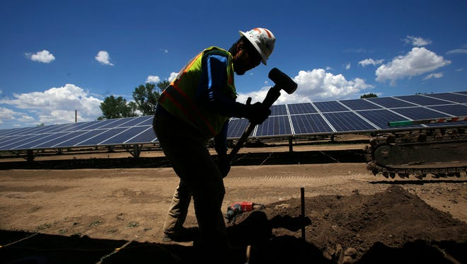 Juan Montoya an electrician with Mosher Enterprises Inc., installs a grounding rod on Monday at the city of Aztec's solar farm project site off Western Drive in Aztec.