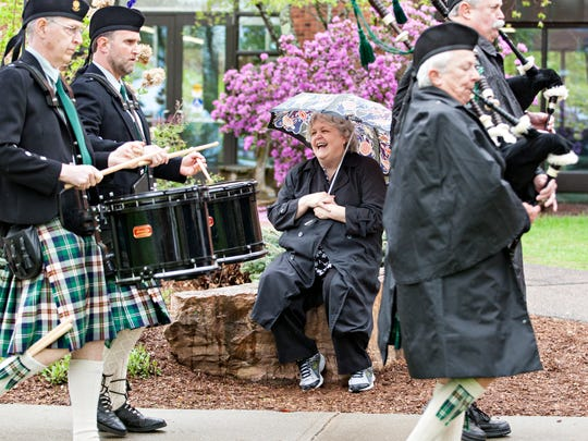 Stephanie Noakes, who works in admissions at St. Michael's College, watches the bagpipers and drummers lead a procession of graduates to commencement ceremonies Sunday, May 14, 2017, on the school's campus in Colchester.