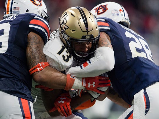 Auburn defensive back Tray Matthews (28) and Auburn linebacker Darrell Williams (49) tackles UCF wide receiver Gabriel Davis (13) during the second half of the Peach Bowl between Auburn and UCF on Monday, Jan. 1, 2018, at Mercedes-Benz Stadium in Atlanta, Ga.