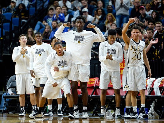The DeLaSalle bench erupts after an and-one opportunity by guard Sage Booker (12) in the first half against Austin  in the Class 3A State Tournament Championship game Saturday, March 25, 2017,  in Minneapolis, Minn.  (Aaron Lavinsky/Star Tribune via AP)