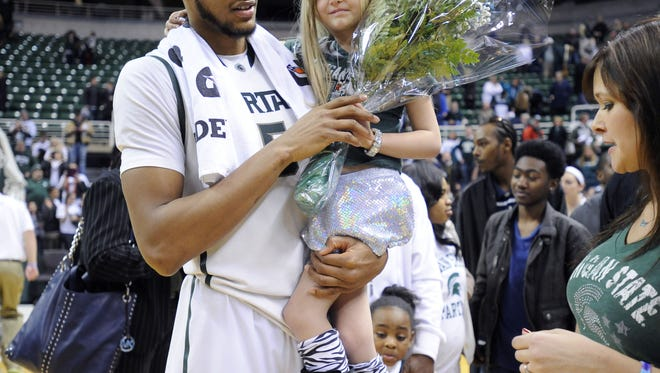 MSU senior Adreian Payne holds Lacey Holsworth, 8, during Senior Day celebrations after MSU's 86-76 win over Iowa at the Breslin Center.