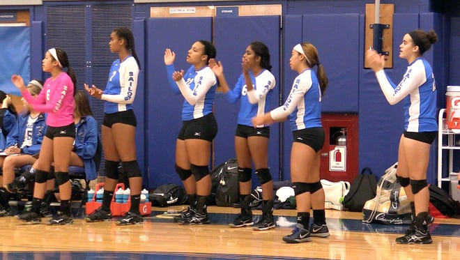 "The Hendrick Hudson volleyball team shouts ""Side Out"" after the team lost a point. The term refers to a team winning a rally in order to get the serve back. When volleyball was played under ""serve to score"" rules, teams could only generate points when they were on offense. Volleyball is now played with ""rally"" scoring, which grants a point to the team that wins the rally, regardless of whether their on offense or defense."