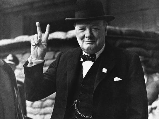 """British Prime Minister Winston Churchill gives a """"Victory"""