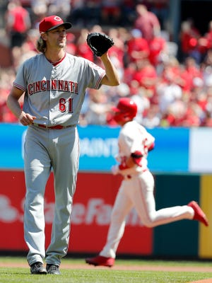 Cincinnati Reds' starting pitcher Bronson Arroyo waits for a new ball as St. Louis Cardinals' Aledmys Diaz rounds the bases after hitting a solo home run during the first inning.