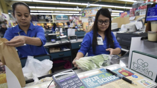 Doris Fiden, left, and Nhez Espinosa check out a customer at the Payless Supermarket in Mangilao on Sept. 29, 2015.