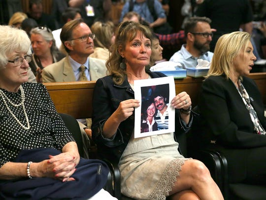 An attendee holds a photo of Cheri Domingo and her