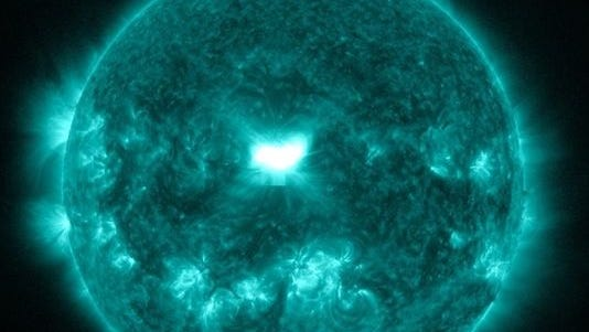 A false-color image of the sun shows the solar flare erupting in the center of the sun earlier Wednesday.