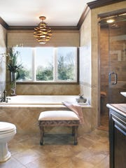 If you have a bathroom with an open view where privacy isn't an issue, you can minimize window treatments and allow ambient light into the room.