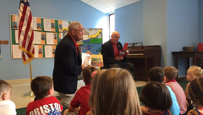 Retired Army generals Dennis Cavin, left, and Thomas Swain read to children at West End United Methodist Church's preschool on Flag Day.