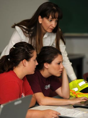Left to right: Civil engineering students Jessica Youngblood and Emily Budagher along with engineering professor Paola Bandini (standing) analyze data they gathered while assessing the condition of a NM road. The program is funded by the DOT.