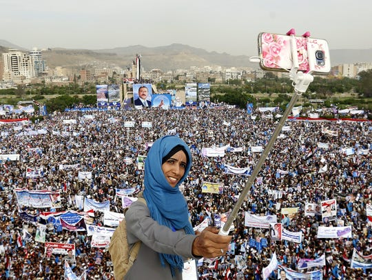 A female supporter of Yemeni ex-president Ali Abdullah Saleh takes a selfie with a smartphone during a rally marking the 35th anniversary celebrations for the formation of Saleh's party in Yemen on Aug. 24, 2017.