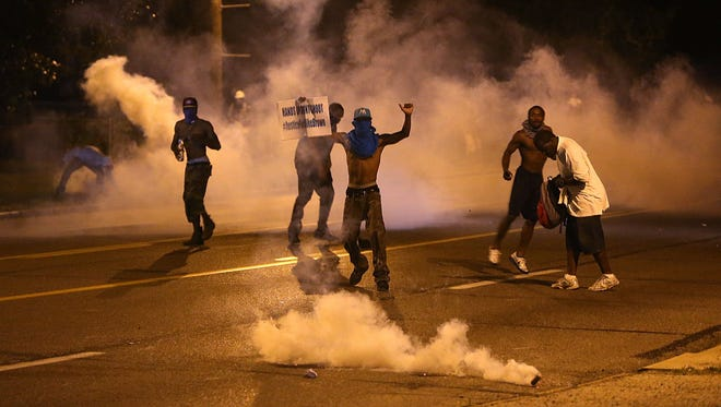 People protest as tear gas canisters detonate around them on Wednesday, in Ferguson, Mo.