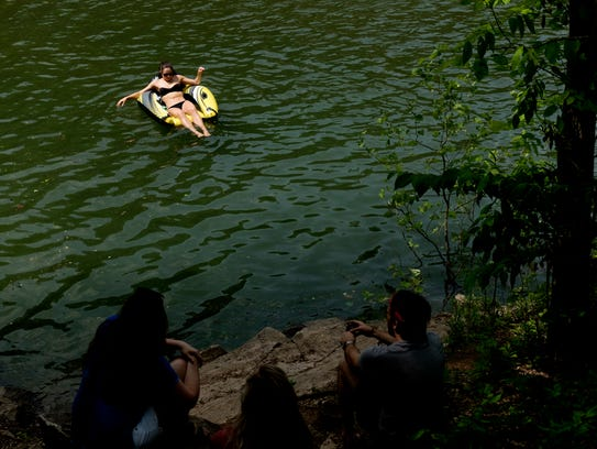 A visitor floats on an inflatable in Meads Quarry Lake