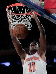 FILE - In this April 9, 2018, file photo, New York Knicks guard Frank Ntilikina (11) dunks against the Cleveland Cavaliers during the fourth quarter of an NBA basketball game, in New York. The NBA will return to London next year with a regular-season game between the Washington Wizards and the New York Knicks. International players on the rosters include Ntilikina, who was born in Belgium to Rwandan parents and grew up in France. (AP Photo/Julie Jacobson, File)