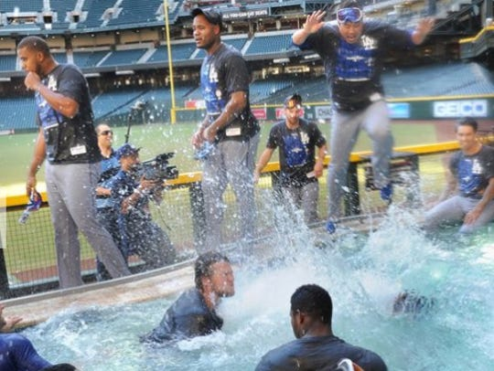 Dodgers players jump into the pool at Chase Field after