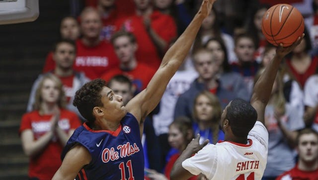 DAYTON, OH - DECEMBER 30: Sebastian Saiz #11 of the Mississippi Rebels contends the shot of Scoochie Smith #11 of the Dayton Flyers at UD Arena on December 30, 2014 in Dayton, Ohio. (Photo by Michael Hickey/Getty Images)