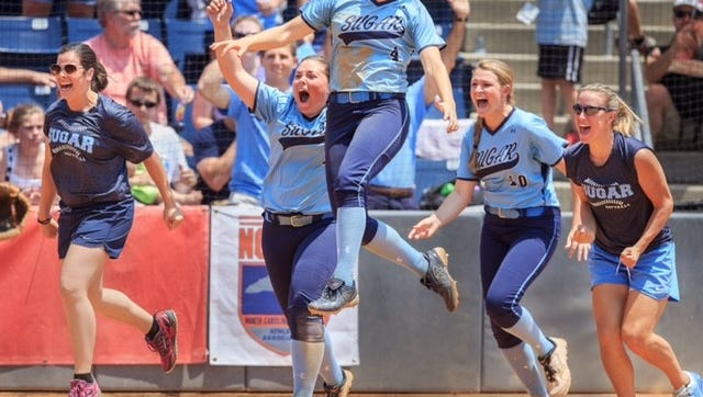 Enka coaches and players celebrate after winning the NCHSAA 3-A softball championship on Saturday in Greensboro.