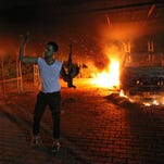 An armed man waves his rifle as buildings and cars are engulfed in flames after being set on fire inside the U.S. consulate compound in Benghazi, Libya, on Sept. 11, 2012.