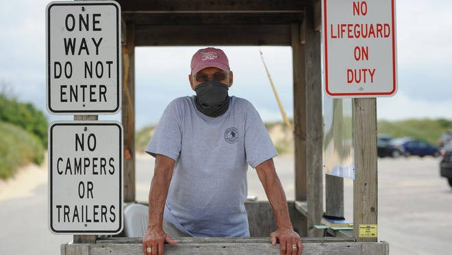 """Ron Edson works the gate Tuesday at First Encounter Beach in Eastham. """"We're in a situation where people just need to be cooperative,"""" he said of the new virus-related protocols."""