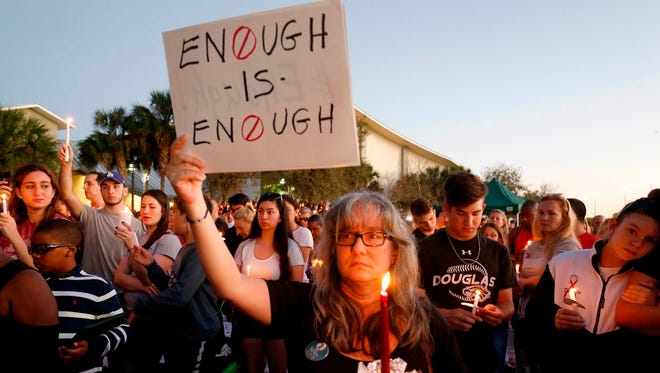 Mourners stand during a candlelight vigil for the victims of Marjory Stoneman Douglas High School shooting in Parkland, Fla. on Feb. 15, 2018.