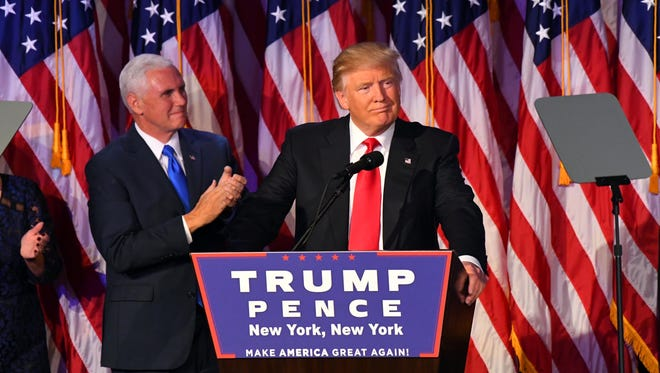 President-elect Donald Trump speaks to supporters early Wednesday, Nov. 9, 2016, at New York Hilton Midtown. Vice President-elect Mike Pence is at left.