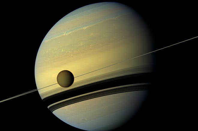 Titan, Saturn's largest moon, passes in front of the giant planet. 513423506