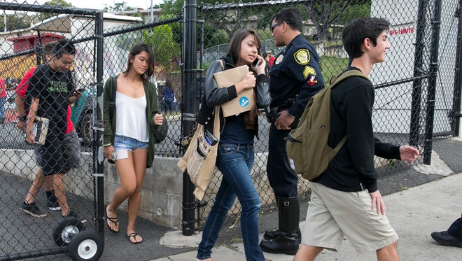 Students leave Roosevelt High School after a shooting on campus Tuesday in Honolulu.