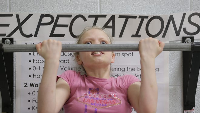 Ava Dodson strains to do pull-ups during a physical education class at Langlade Elementary School in Allouez.