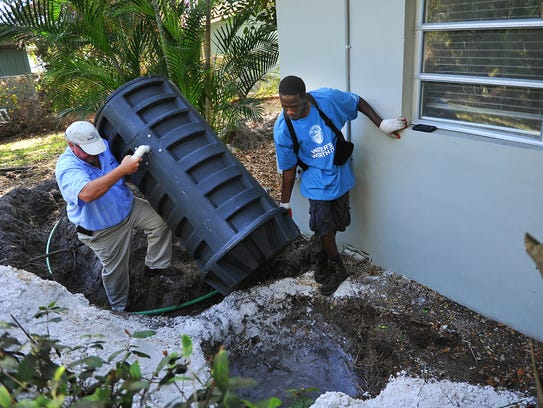Cornelius Kossen (left), of the Stuart Public Works Department, and Holwinster Alexis install a grinder tank in 2015 at a home on Osceola Street in Stuart. The system grinds sewage which is pumped through a 1.25-inch hose also buried in the yard into an established sewer line.