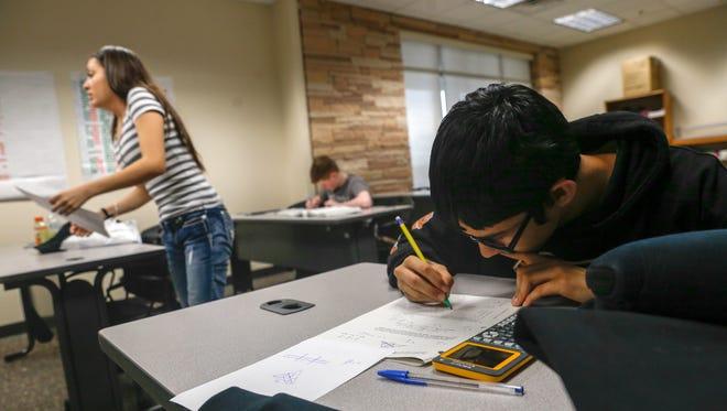 Jaden Mascarenas, right, works on his geometry homework on Friday at San Juan College High School in Farmington.