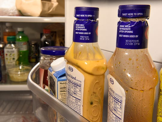 Bottles of expired salad dressing and other items sit