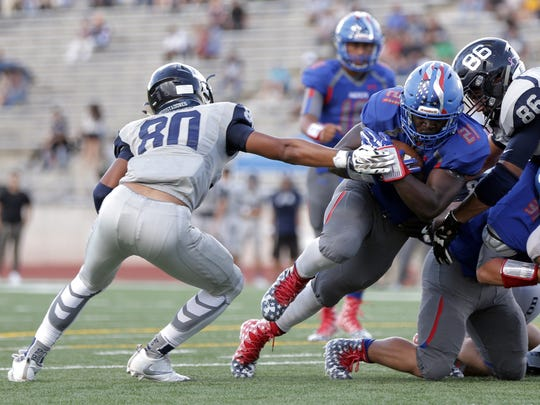 Americas running back Joshua Fields breaks past Del Valle's Nicholas Sparks on his way to over 170 yards in his season opener Aug. 25 at the Socorro Student Activities Complex.