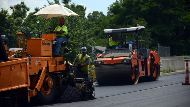 Employees with Kokosing pour a layer of asphalt onto South Ewing Street Monday, June 12, 2017, in Lancaster.
