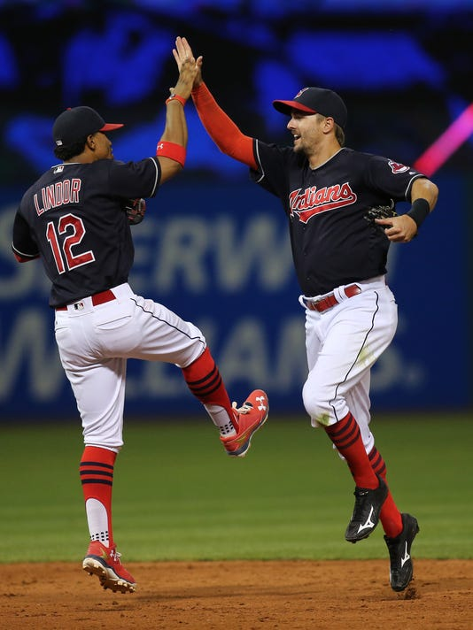Cleveland Indians' Francisco Lindor (12) high-fives Lonnie Chisenhall after defeating the New York Yankees in a baseball game Friday, July 8, 2016, in Cleveland. (AP Photo/Aaron Josefczyk)