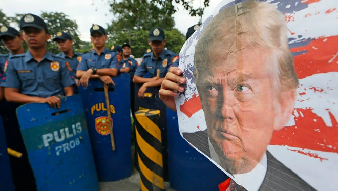 Protesters display a photo of President-elect Donald Trump during an anti-U.S. protest outside the U.S. Embassy in Manila on Nov. 10, 2016.