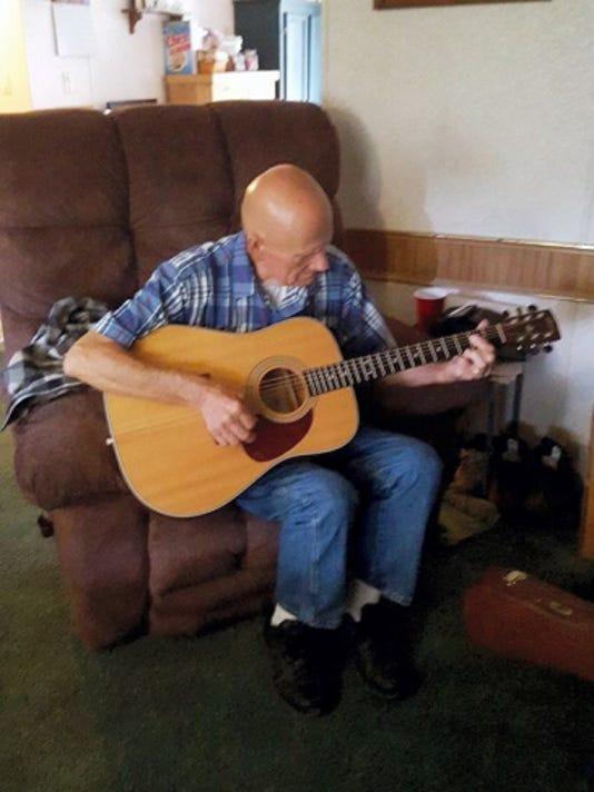 """John """"Dave"""" Mellott plays his guitar — his favorite hobby."""