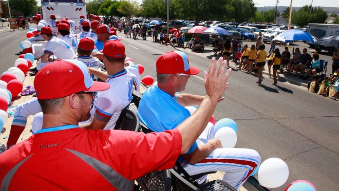 Jim Chamblee, one of the coaches for D-Bat Elite, waves to the crowd during the Connie Mack World Series parade on July 15, 2016, in downtown Farmington. This year's parade takes place at 10 a.m. Friday