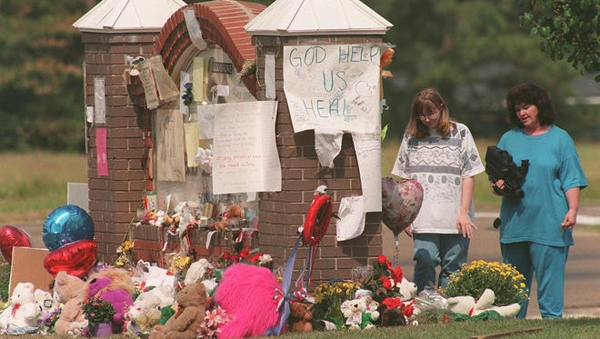 Mourners drop off items at a memorial site for the victims of the Pearl High School shooting in 1997.