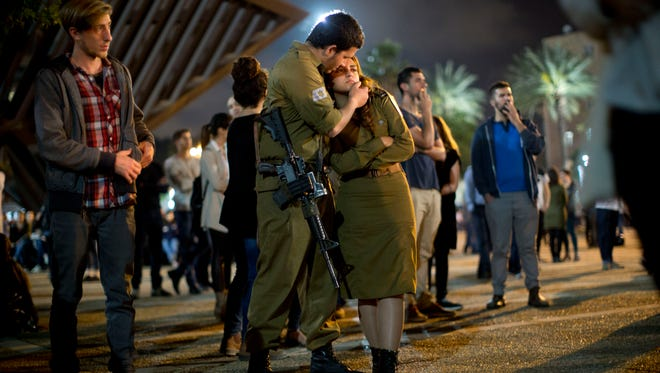 Israeli soldiers and other Israelis attend a ceremony marking Israel's annual Memorial Day for fallen soldiers, in Tel Aviv, Israel, Tuesday, April 21, 2015.