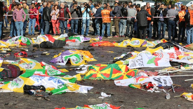 Bodies of victims are covered with flags and banners at the site of an explosion in Ankara, Turkey, Oct. 10, 2015.
